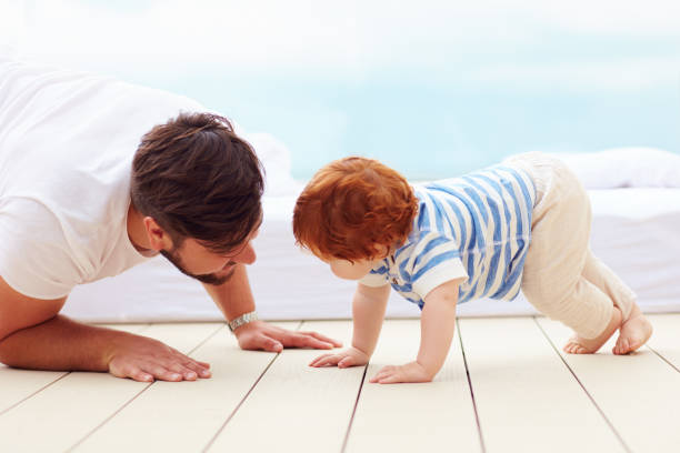 father playing with his little son on the floor stock photo