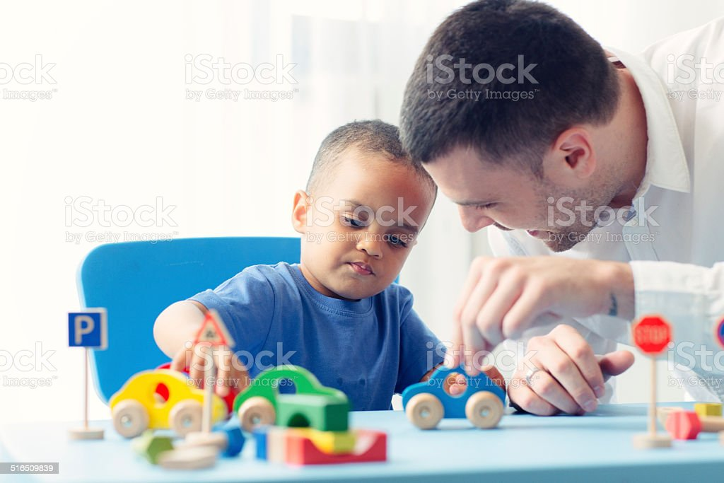 Father Playing With His Son At Home. stock photo