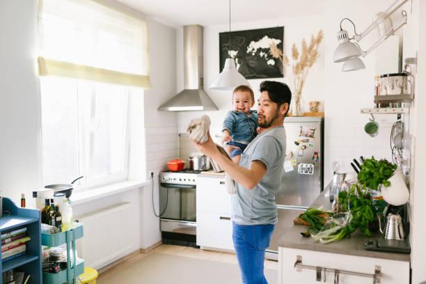 vater spielt mit seinem sohn in der küche - hausmannskost stock-fotos und bilder
