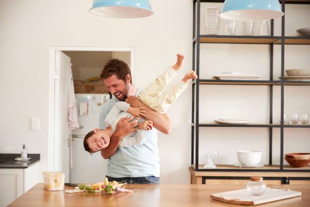 vater mit sohn zu spielen, wie sie in der küche speisen zubereiten - kochinsel stock-fotos und bilder