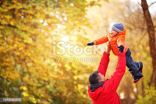istock Father playing with son on sunny day in autumn 1043580532