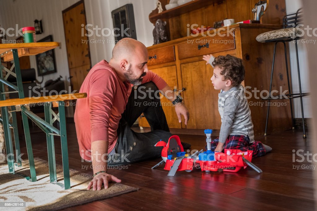 Father playing with son sitting on the floor stock photo