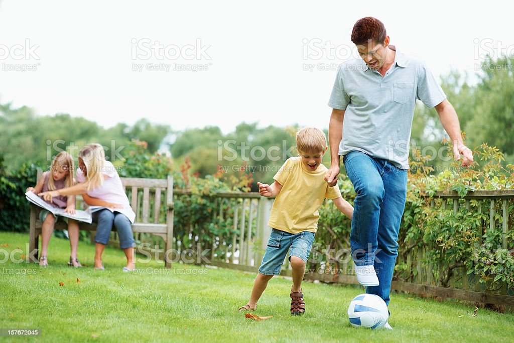 Father playing with son while mother and daughter sitting together royalty-free stock photo