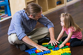 A little girl with down syndrome sitting on the floor in a playroom with her father playing with a toy.  They are both touching the colorful plastic puzzle pieces in front of them and looking at each other.