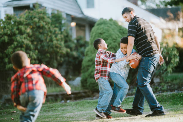 Father Plays Football Outside With His Sons stock photo