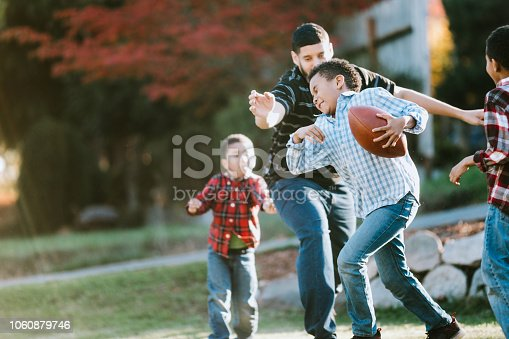 A dad and his three boys play American foot ball in their front yard, having fun spending family time together.