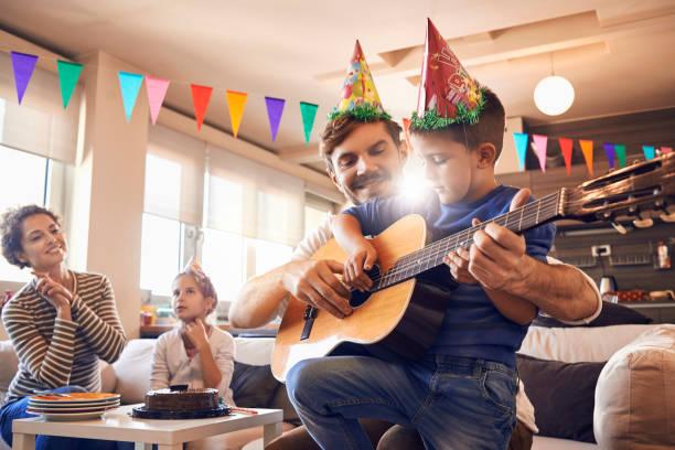vater spielt gitarre mit seinem sohn und feiert geburtstag - gitarren geburtstagstorten stock-fotos und bilder