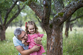 Father plays hide and seek with his daughter. He found her near the tree.
