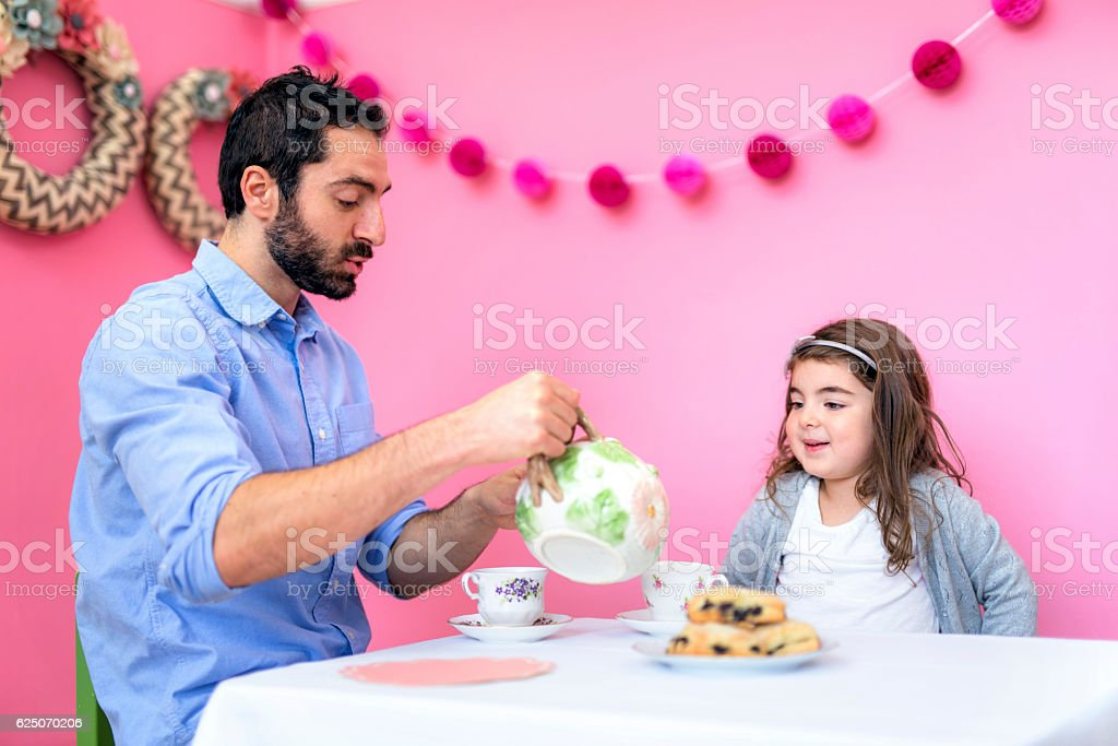 Father pouring a cup of tea for his daughter stock photo