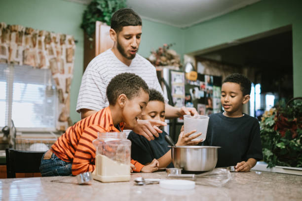 Father Prepares Meal in Kitchen With His Sons stock photo
