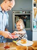 istock Father preparing a hamburger bun with his cute little son 1329256110
