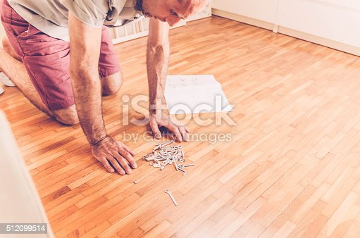 istock Father preparing baby cot; screws and tools on the floor 512099514