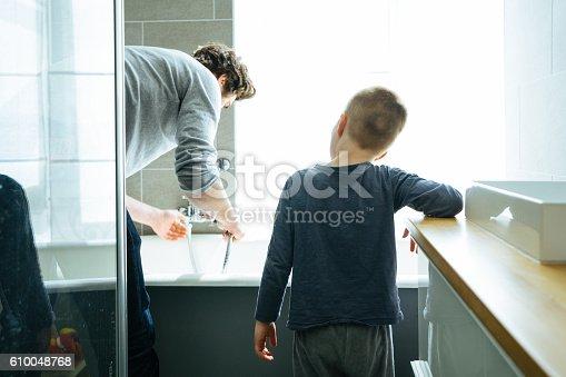 Father preparing the bathtub for his son.