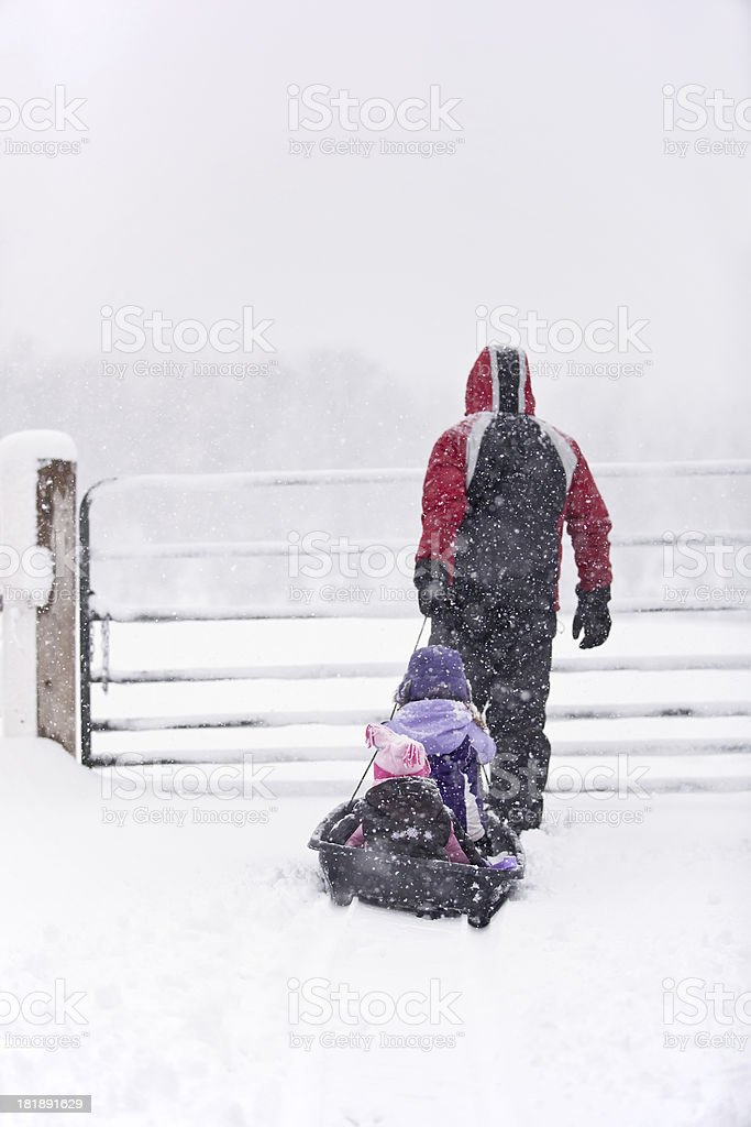 Father Pulling Daughters in Sled on Ranch royalty-free stock photo