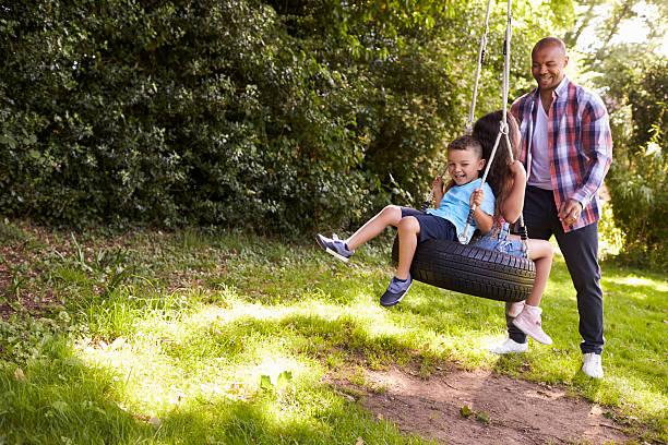 father pushing children on tire swing in garden - balouço imagens e fotografias de stock