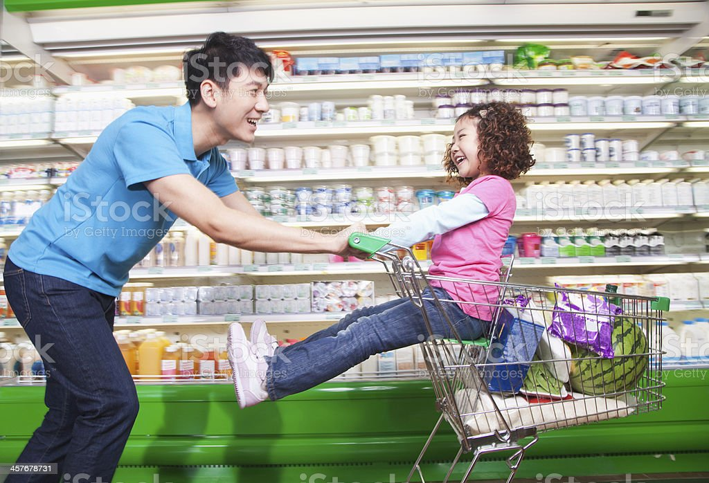 Father Pushing Daughter in Shopping Cart Inside Supermarket, Laughing stock photo