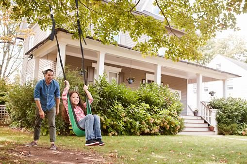 Father Pushing Daughter On Garden Swing At Home - Fotografie stock e altre immagini di 8-9 anni