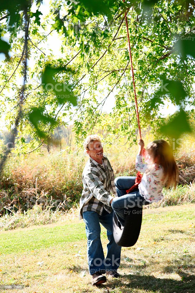 father pushing daughter on tire swing royalty-free stock photo