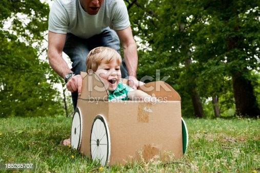 496487362 istock photo Father pushing his son in a cardboard box on grass 185265707