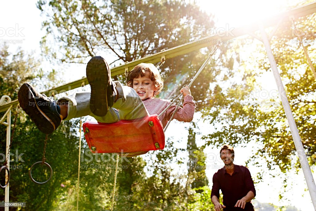 Father pushing son on swing in park - foto stock