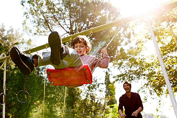 Father pushing son on swing in park stock photo