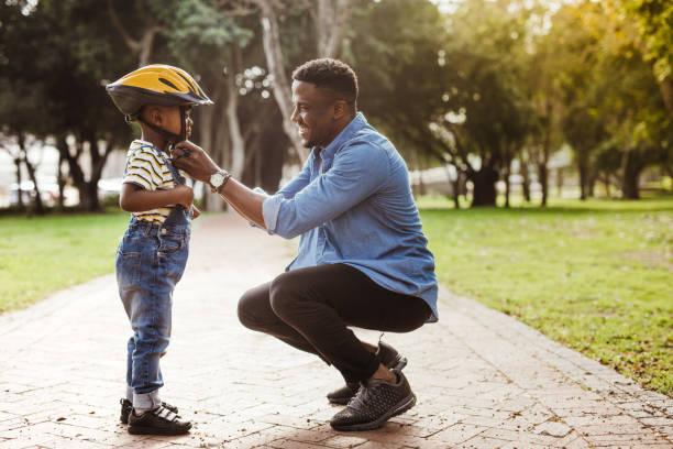 father puts his son a helmet for riding bike - kask sportowy zdjęcia i obrazy z banku zdjęć