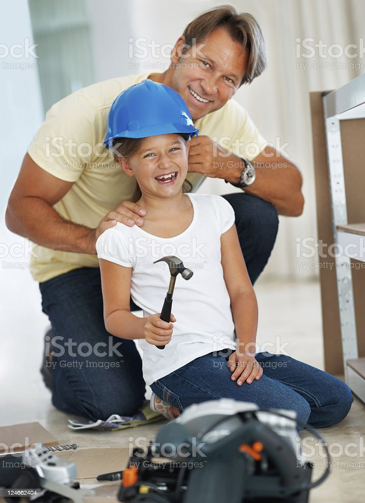 Father putting a helmet on his daughter's head royalty-free stock photo