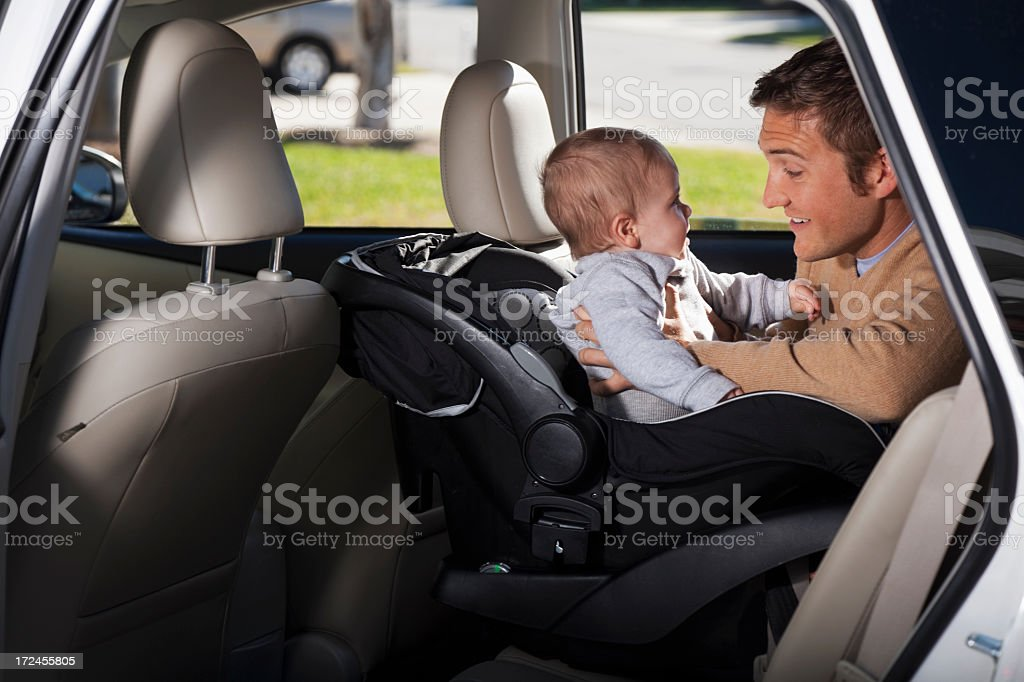 Father putting baby in car seat royalty-free stock photo
