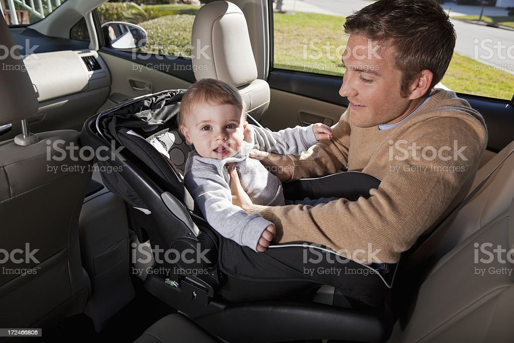 Father putting baby in car seat stock photo