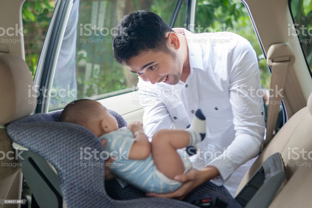 Father Putting his Baby on Car Seat stock photo