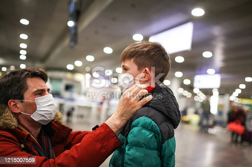 father putting medical mask on his son to protect himself from the coronavirus in an airport terminal or shopping mall