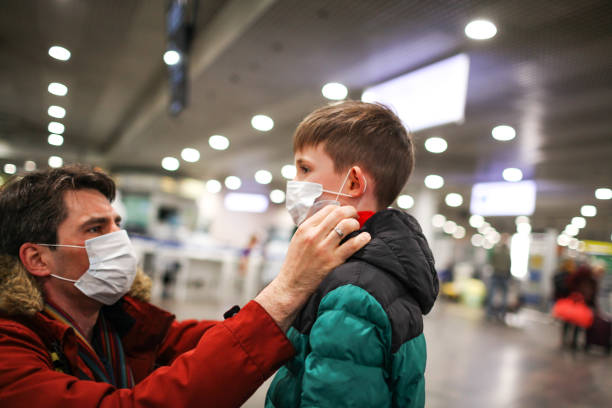 father putting medical mask on his son to protect himself from the coronavirus in an airport terminal or shopping mall - covid flight imagens e fotografias de stock