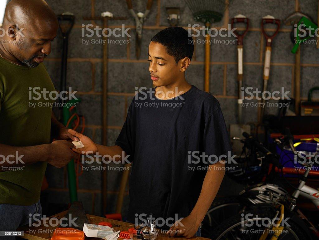 Padre mettendo gesso su adolescente di canto foto stock royalty-free