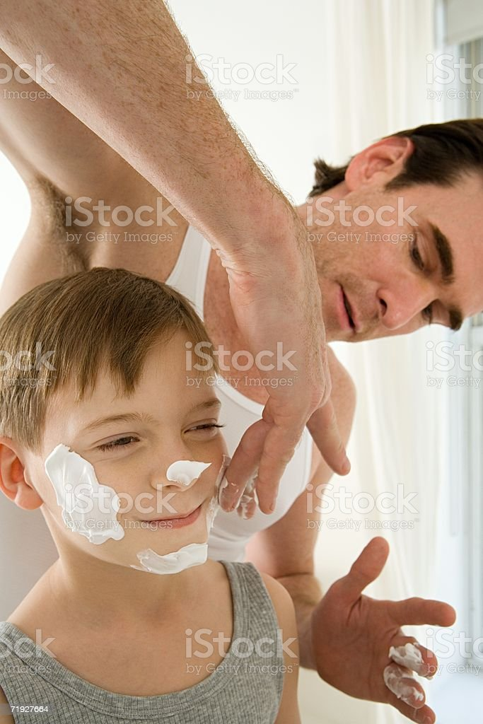 Father putting shaving cream on son royalty-free stock photo