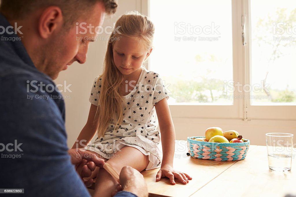 Father Putting Sticking Plaster On Daughter's Knee stock photo
