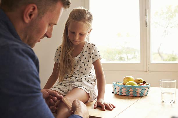 father putting sticking plaster on daughter's knee - pansement adhésif photos et images de collection