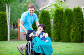 istock Father racing around park with disabled son in wheelchair 495857823