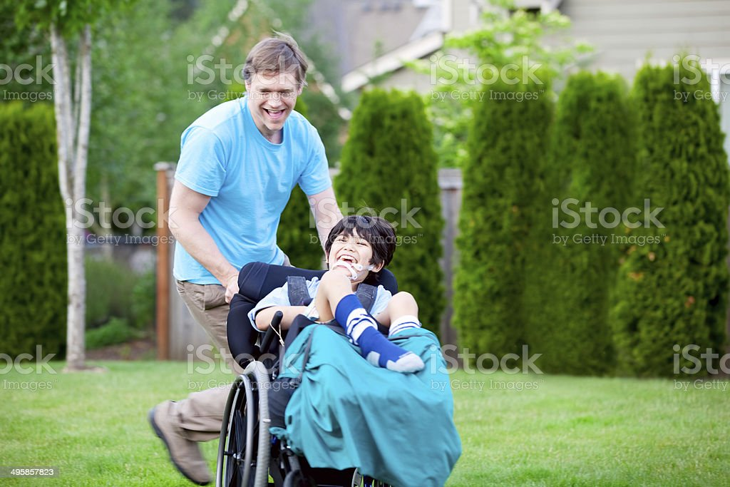 Father racing around park with disabled son in wheelchair stock photo