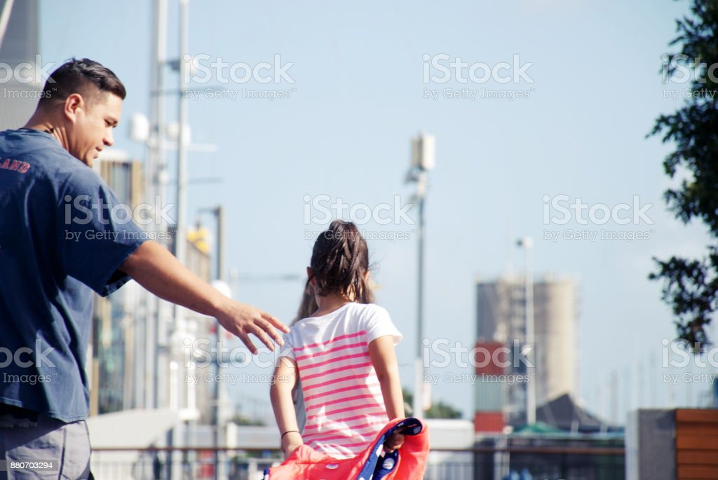 Father Reaches to Help Daughter in Urban Scene stock photo