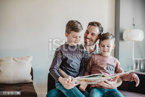 Father is at home with his sons in his leap and he is reading a book to them