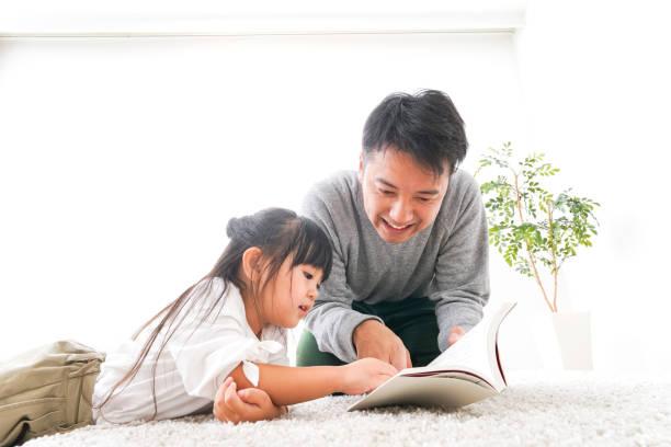 父は子供に本を読んでいる ストックフォト