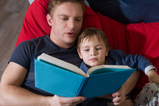 Father reading a story to his little son. happy family time together at home. stock photo