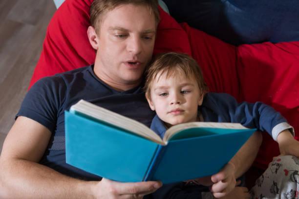 padre leyendo un cuento a su pequeño hijo. familia feliz tiempo juntos en casa. - intergénero fotografías e imágenes de stock