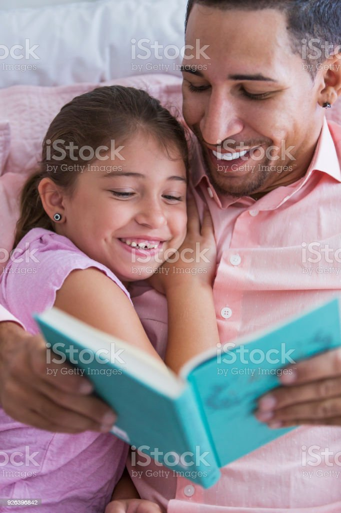 Father reading bedtime story to little girl stock photo