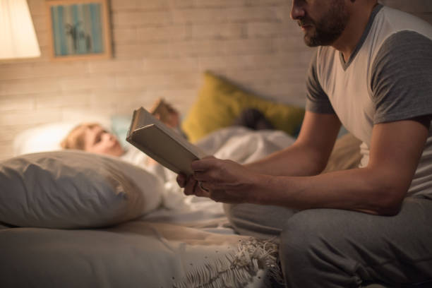Father Reading Bedtime Story to Son stock photo