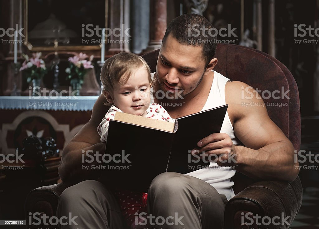 Father reading book to daughter stock photo