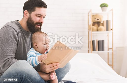 istock Father reading book to little baby son 1084535408