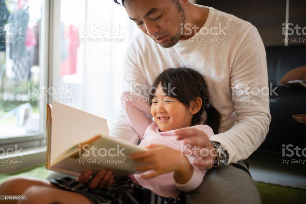 父娘自宅で本を読んで ストックフォト