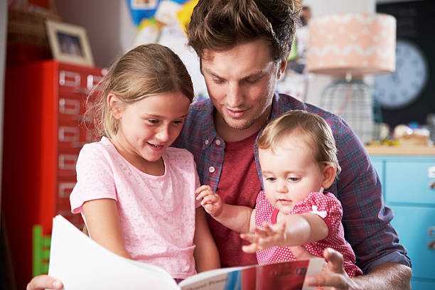 Father Reading Book With Daughters In Bedroom stock photo