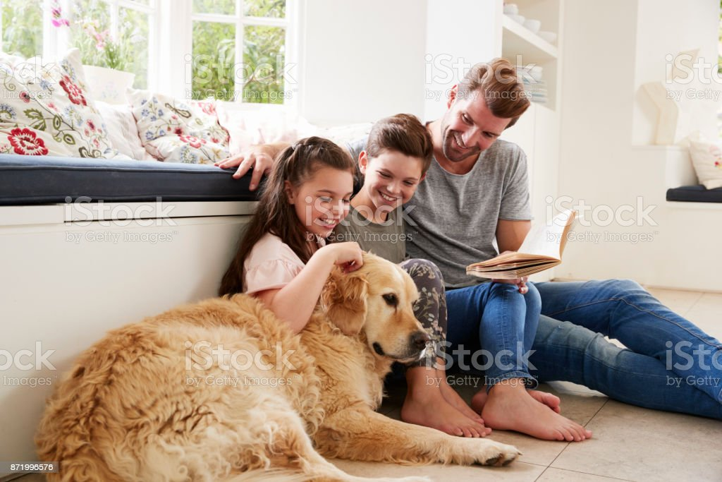 Father Reading Book With Son And Daughter And Pet Dog At Home stock photo